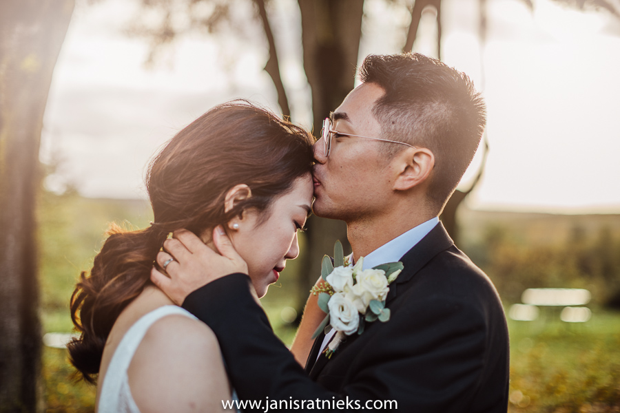 groom kissing the bride on forehead