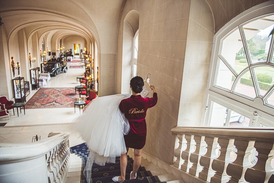 Bride carrying her wedding dress