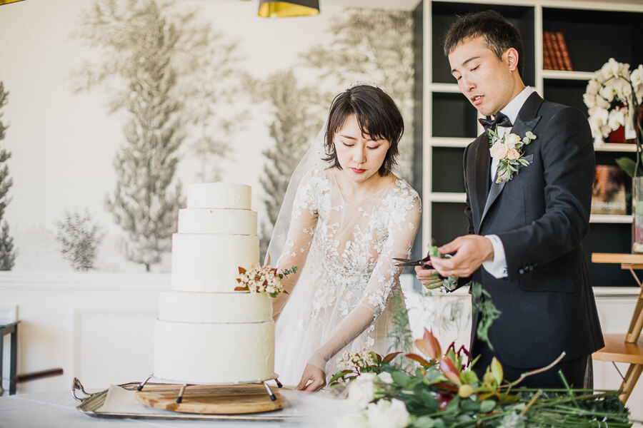 bride and groom decorating their own cake